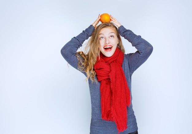 그녀의 머리 위에 오렌지 과일을 들고 금발 소녀입니다.