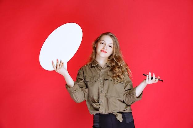 Ragazza bionda che tiene un ideaboard ovale in una mano e uno smartphone in un'altra mano.