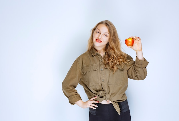 Blonde girl holding and promoting a red peach.