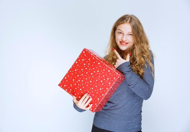 Ragazza bionda che tiene un grande contenitore di regalo rosso.