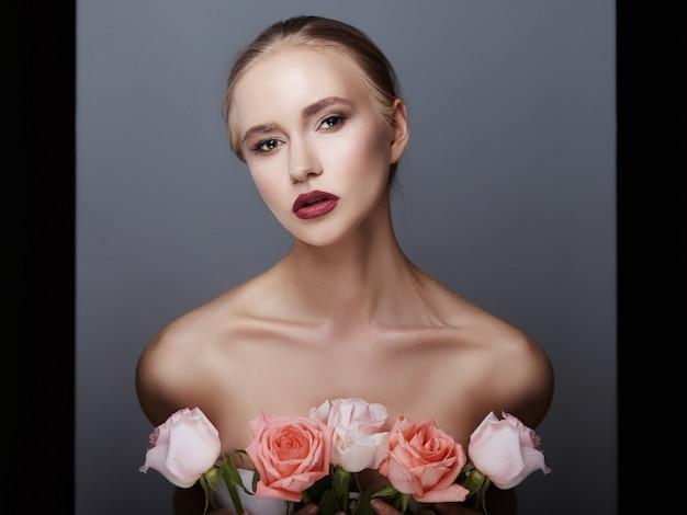 Blonde girl holding rose flowers near face. beauty