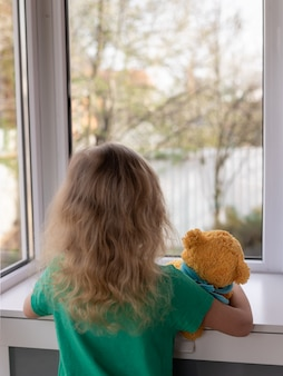 Blonde girl holding a teddy bear and looking out the window at the garden