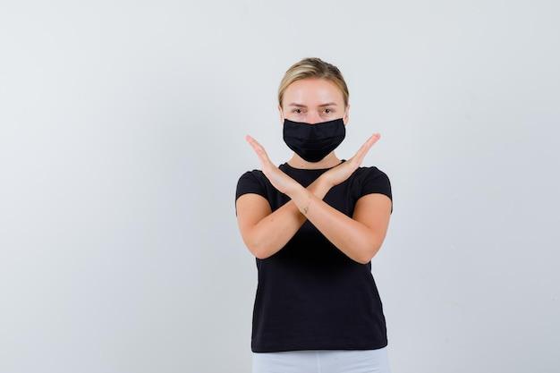 Ragazza bionda che tiene due braccia incrociate, gesticolando nessun segno in maglietta nera isolata