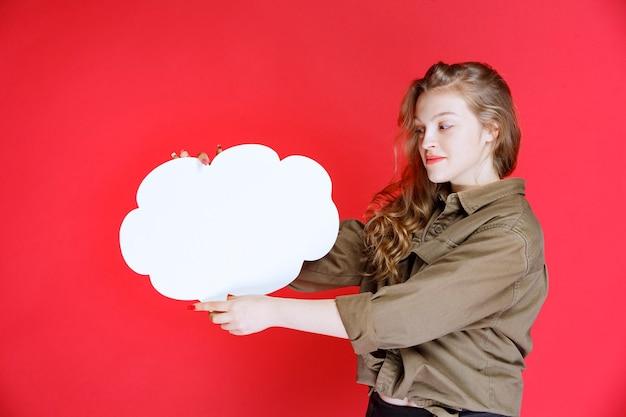 Ragazza bionda che tiene un ideaboard in bianco di forma della nuvola bianca.