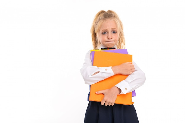 Blonde girl holds books against a white wall