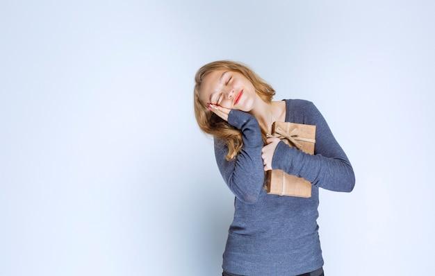 Белокурая девушка плотно обнимая ее картонную подарочную коробку.