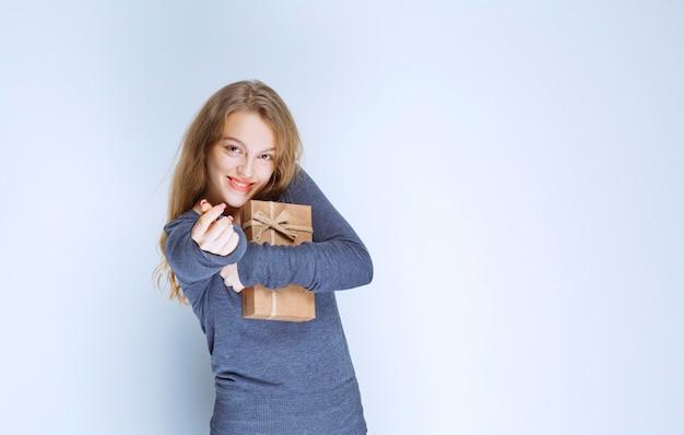 Blonde girl hugging her cardboard gift box tight.
