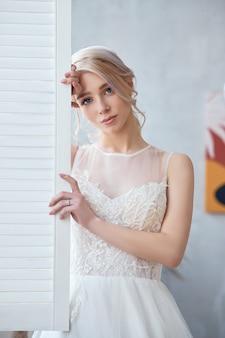 美しい白いウェディングドレスのブロンドの女の子。結婚式の前に女性の花嫁が新郎を待っています