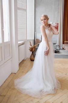 美しい白いウェディングドレスのブロンドの女の子。女性の花嫁は結婚式の前に新郎を待っています
