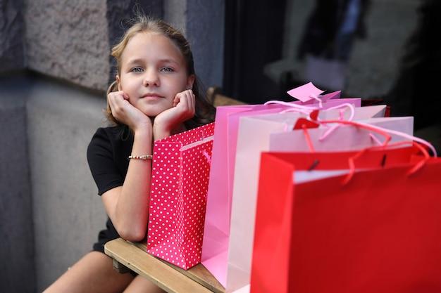 街で色付きのバッグと座っている黒いドレスのブロンドの女の子