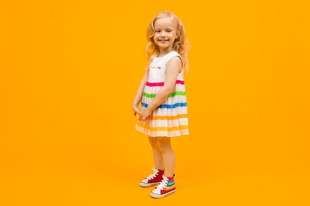 明るい縞模様の夏のドレスのブロンドの女の子