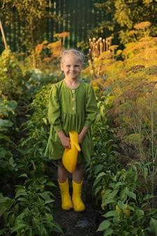 녹색 드레스와 노란 부츠를 신은 금발 소녀가 식물에 물을 주는 정원에 서 있다