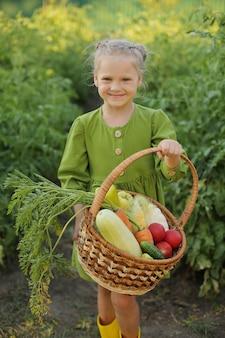 녹색 드레스와 노란 부츠를 신은 금발 소녀는 정원에 서서 고른 야채를 들고 있다