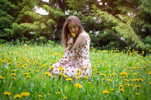明るいドレスを着たブロンドの女の子は、晴れた日の市立公園で明るい花の花束を収集します