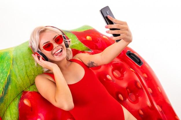 Белокурая девушка в красном купальнике и темных очках сидит на плавательном матрасе и слушает музыку в наушниках и держит телефон в руках