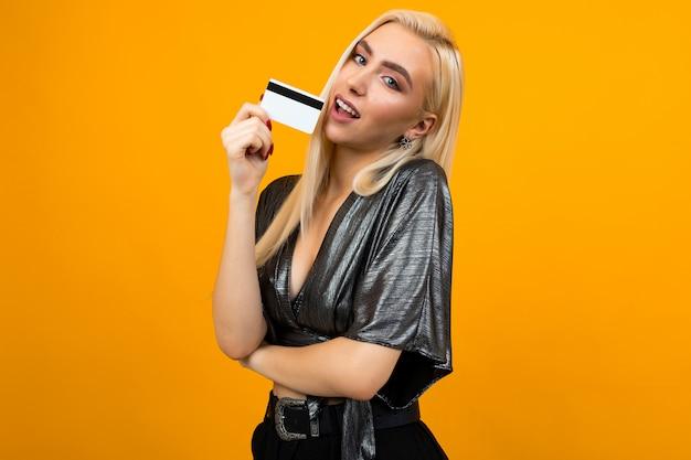 Блондинка в блестящей блузке держит кредитную карту