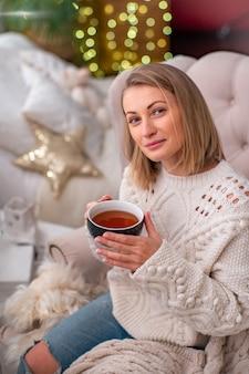Блондинка в свитере с чашкой чая сидит на кровати