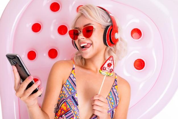 Блондинка в купальнике и темных очках с леденцом и телефоном в руках на плавательном матрасе слушает музыку в наушниках
