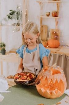 할로윈을 위해 호박으로 장식된 부엌에서 앞치마를 입은 금발 소녀가 포카치아 파이를 준비합니다