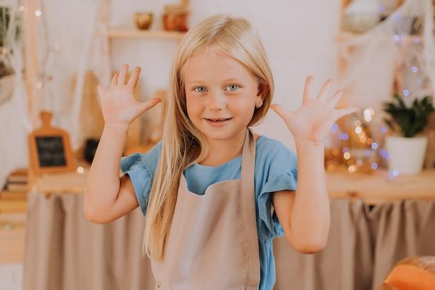 할로윈 호박으로 장식된 부엌에서 앞치마를 입은 금발 소녀가 포카치아 파이를 준비합니다