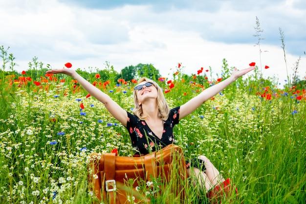 Блондинка в красивом платье с чемоданом в поле маков в летнее время
