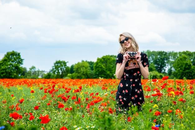 여름 시간에 양 귀 비 필드에 빈티지 카메라와 함께 아름 다운 드레스에 금발 소녀