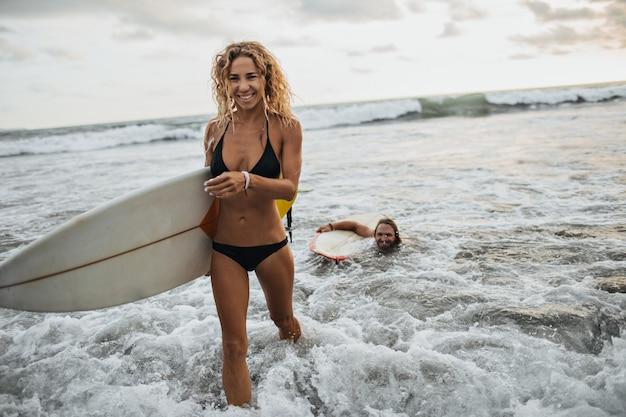 黒の水着のブロンドの女の子はサーフボードを保持します