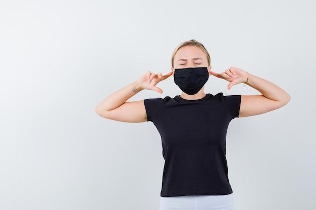 Блондинка в черной футболке, белых штанах, черная маска, затыкающая уши, изолированные