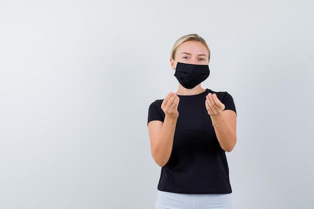 검은 티셔츠, 흰 바지, 고립 된 이탈리아 제스처를 보여주는 검은 마스크에 금발 소녀
