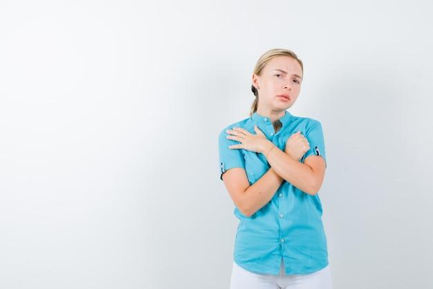 파란색 블라우스에 금발 소녀, 두 팔을 들고 흰 바지는 고립 된 교차