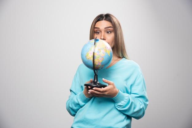 地球儀を持って驚いたように見える青いスウェットシャツのブロンドの女の子。
