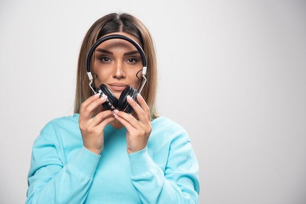 Блондинка в синей толстовке держит наушники и готовится носить их, чтобы слушать музыку.