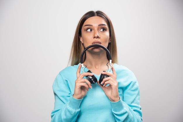 ヘッドフォンを保持し、音楽を聴くためにそれらを着用する準備ができて青いスウェットシャツのブロンドの女の子