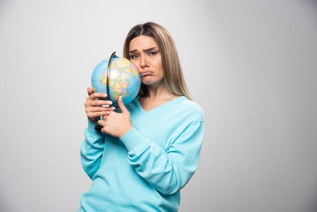 青いスウェットシャツのブロンドの女の子は地球儀を持っており、不確かで混乱しているように見えます。
