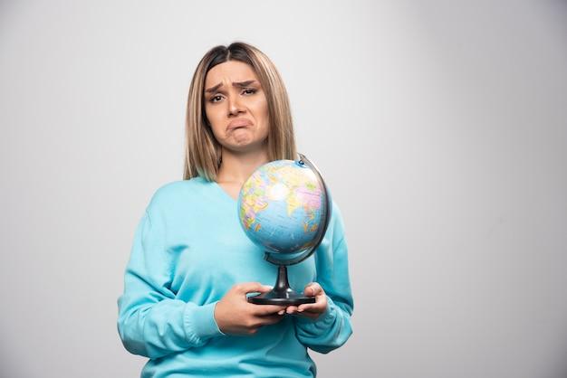 Блондинка в синей толстовке держит глобус и выглядит неуверенно и смущенно.