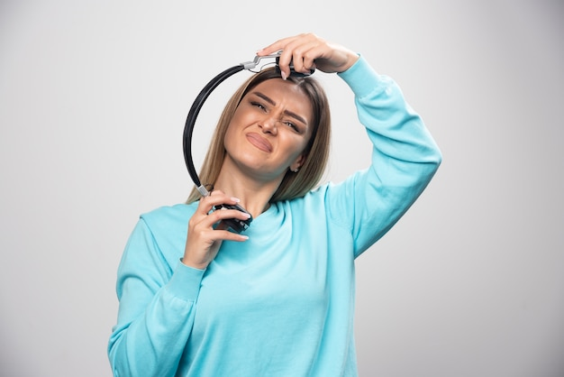 青いセーターのブロンドの女の子はヘッドフォンを聞いて音楽を楽しんでいません
