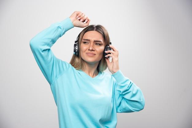 헤드폰을 착용하고 음악을 즐기고 재미 파란색 셔츠에 금발 소녀.