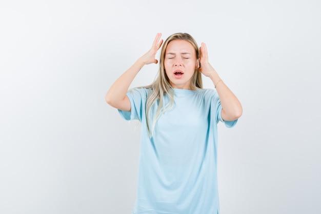 Блондинка в синей футболке держится за руки возле головы и выглядит раздраженной, вид спереди.