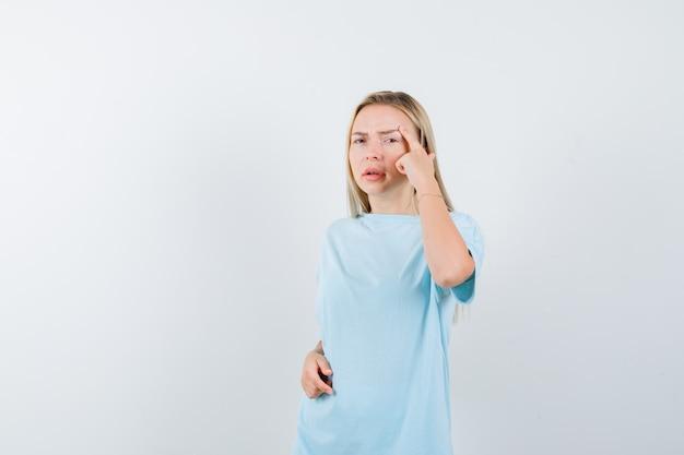 寺院に人差し指を置き、物思いにふける、正面図を探している青いtシャツのブロンドの女の子。