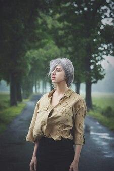 Блондинка в депрессии на сельской дороге в дождливый день