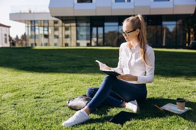 眼鏡のブロンドの女の子は芝生に座って、本で働く