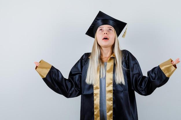 대학원 제복을 입은 금발 소녀는 팔을 펼치고 감사하는 동안 위쪽으로보고