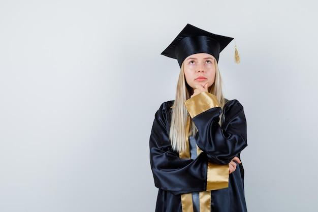 Блондинка в униформе выпускника подпирает подбородок рукой и смотрит задумчиво
