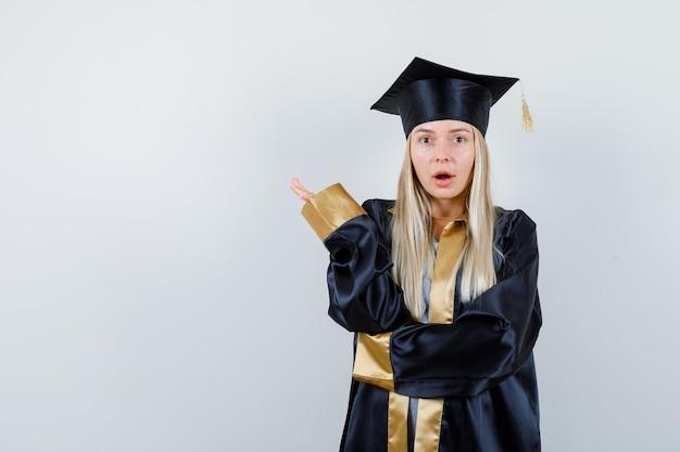 Блондинка в униформе выпускника поднимает руку, открывает рот и выглядит озадаченной