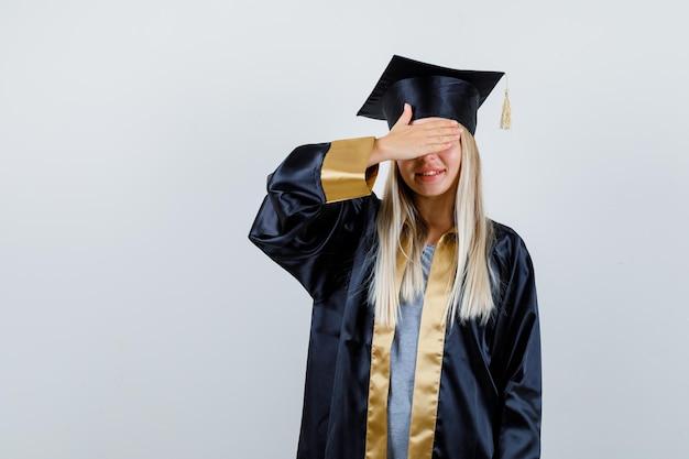 目を覆い、幸せそうに見える卒業式のガウンとキャップのブロンドの女の子