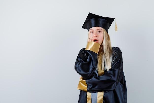 卒業式のガウンとキャップのブロンドの女の子は、口の近くに手を置き、驚いて見えるように肘に手を保持