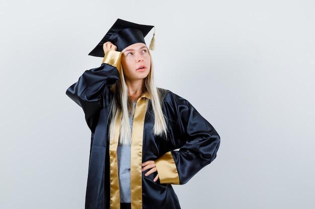卒業式のガウンと帽子のブロンドの女の子が腰に手を握り、頭に手を置き、目をそらし、自信を持って見える