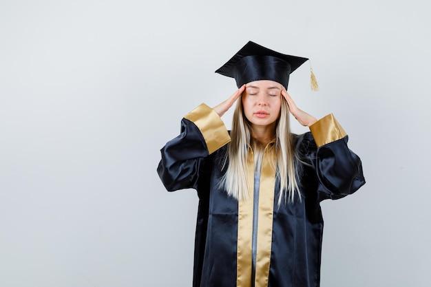 졸업 가운과 사원에 손을 잡고 모자에 금발 소녀, 눈을 감고 진정 찾고