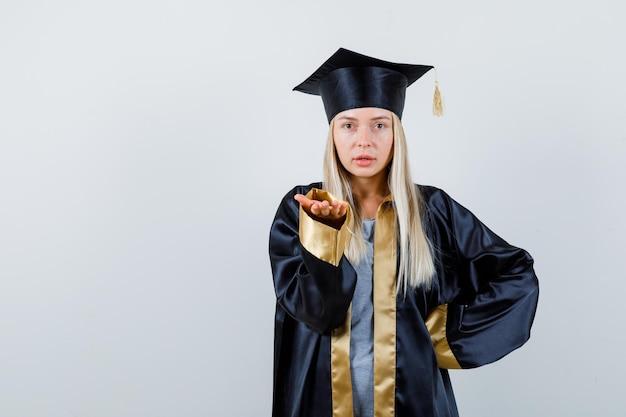 卒業式のガウンとキャップのブロンドの女の子は、片方の手を腰に持ち、何かを持って魅力的に見えるようにもう一方の手を伸ばします