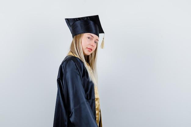 卒業式のガウンとキャップのブロンドの女の子が肩越しに見て、カメラでポーズをとって、かわいく見える